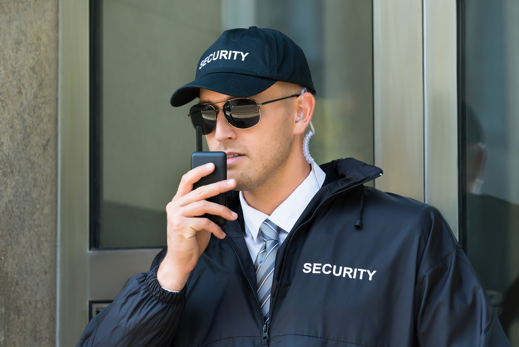 Portrait Of Young Security Guard Using Walkie-talkie Radio