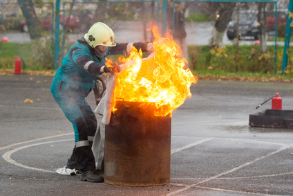 Fireman in special clothes extinguishes the fire in a barrel with a cloth
